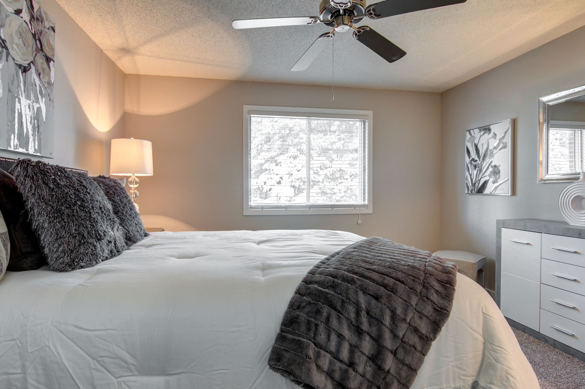 Colonial Estates bedroom with a queen bed and closet with grey and white decor.