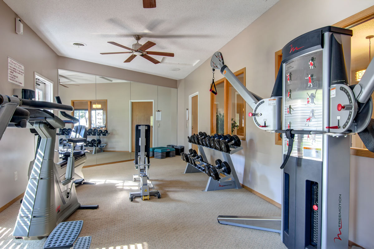 Indoor gym with equipment and mirrored wall