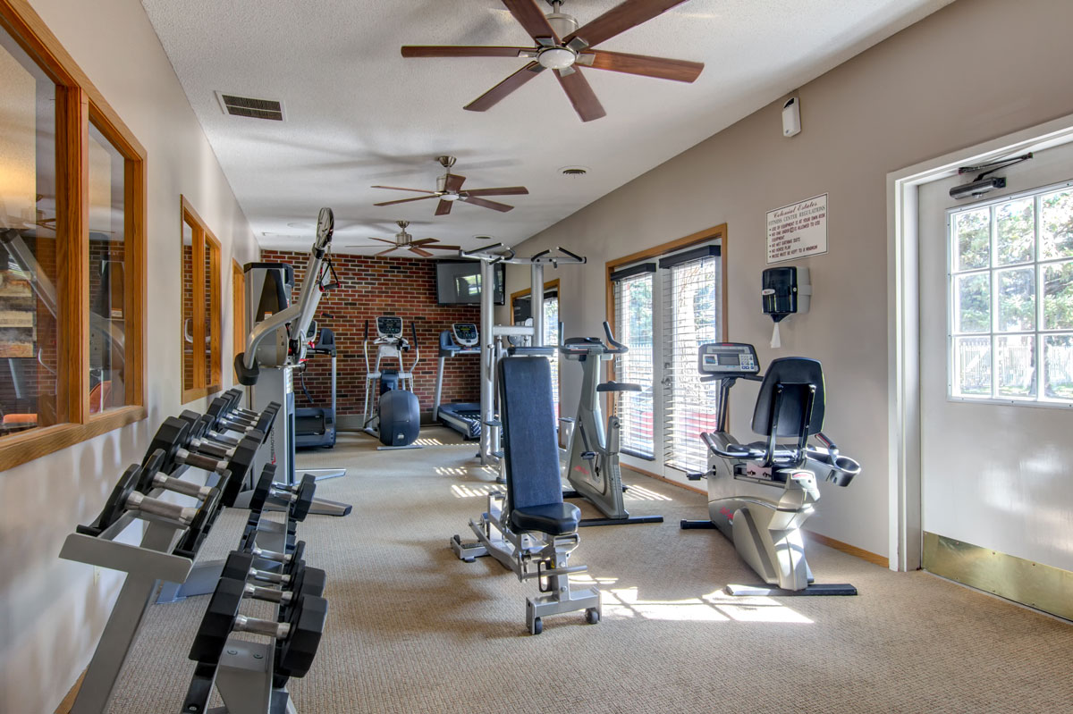 Indoor gym with equipment and brick wall