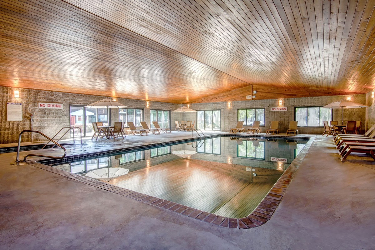 Large indoor pool with spacious deck and multiple seating.