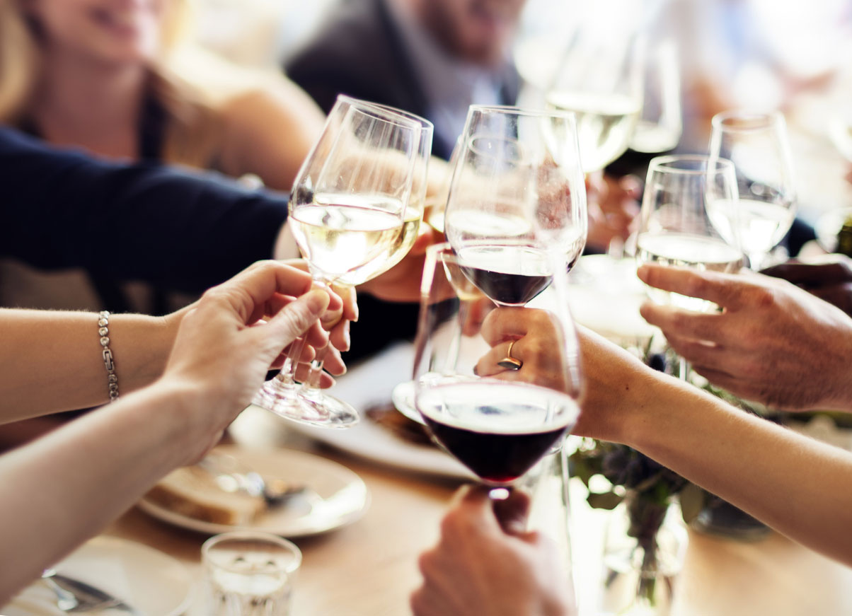 A group of people holding up their wine glasses to cheers