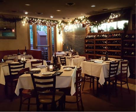 italian restaurant with twinkle lights and wine bottles on a rack