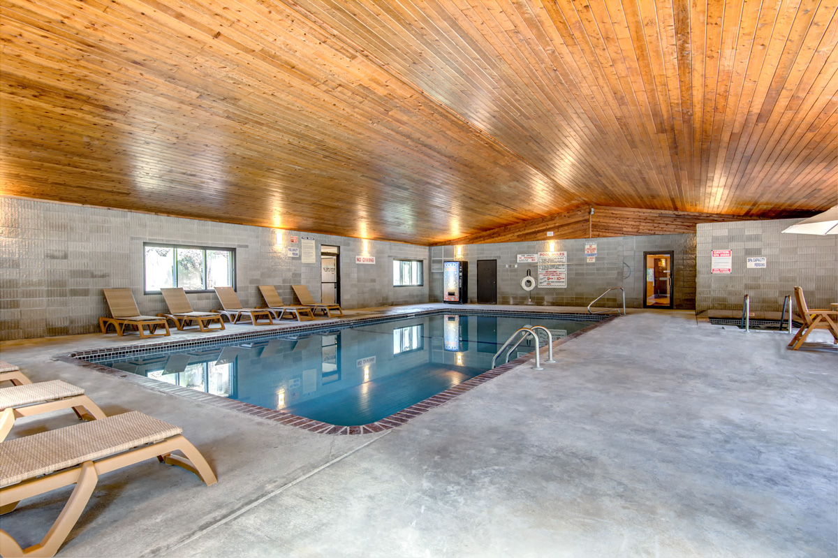 large indoor pool with spacious deck and multiple seating