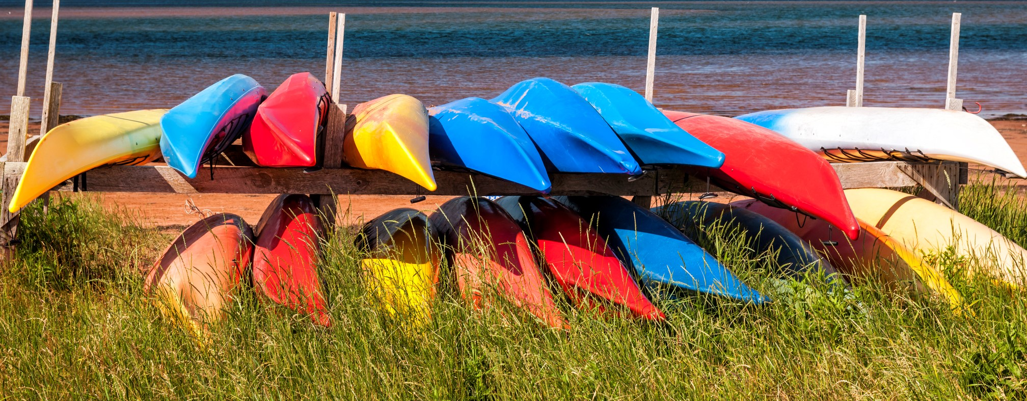 Colorful kayaks stored on Atlantic shore in North Rustico, Prince Edward Island, Canada
