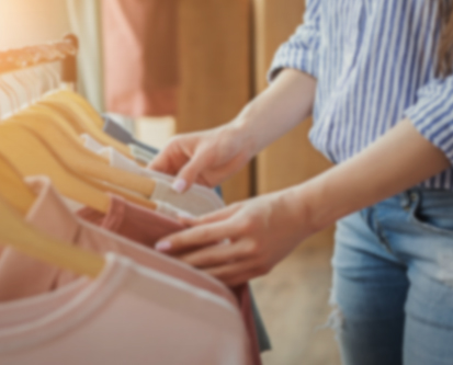 Woman in a striped shirt looking through a rack of clothes.